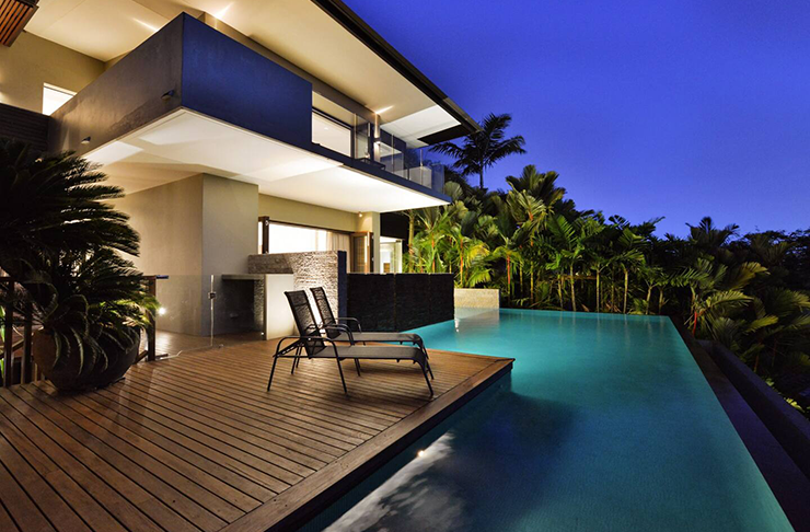 A three-story mansion lit up at night and surrounded by a wrap-around pool.