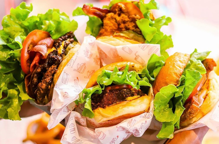 Four takeaway burgers, two beef and two chicken, bursting with bright salad and tomato.