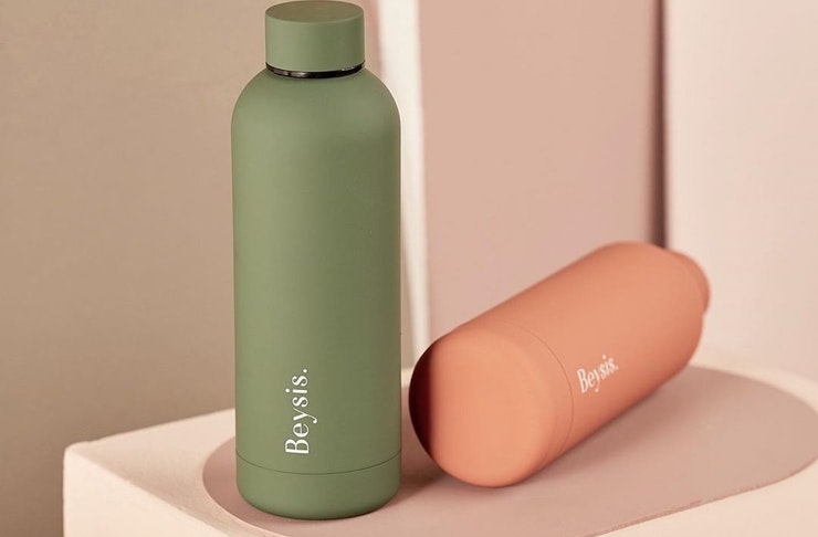 A sleek green and peach water bottle lie side by side.