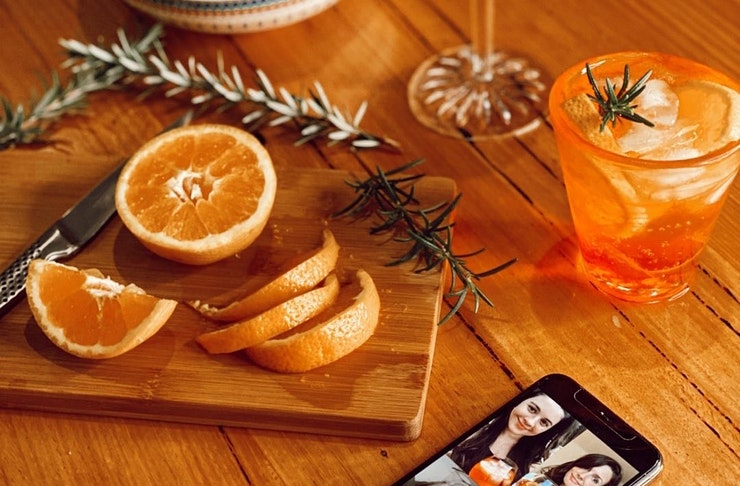 An Aperol Spritz sits next to orange slices and a phone.