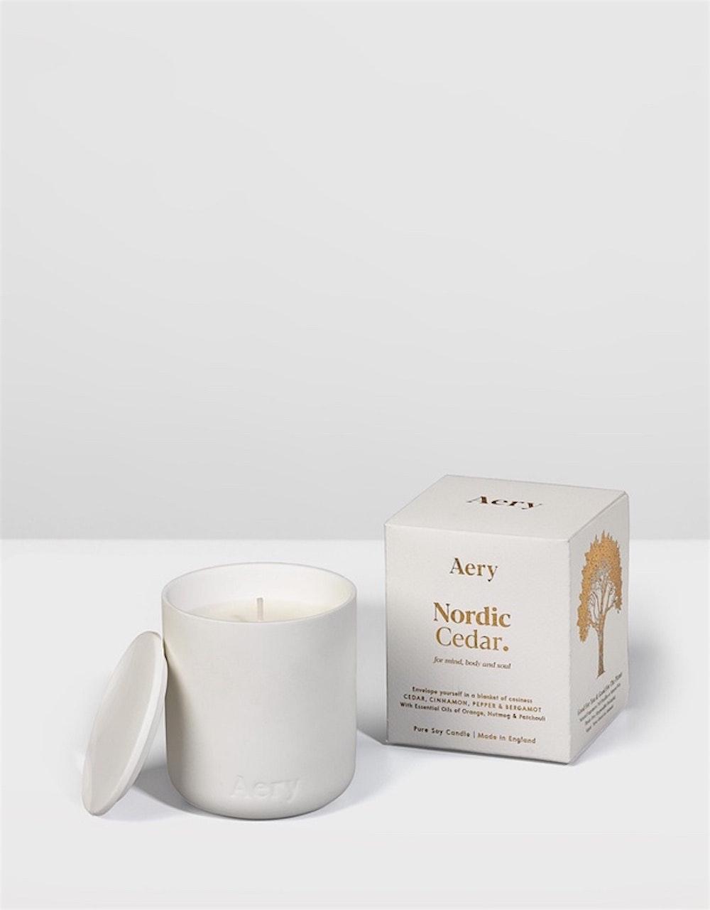 A matte white candle sits beside a white box.
