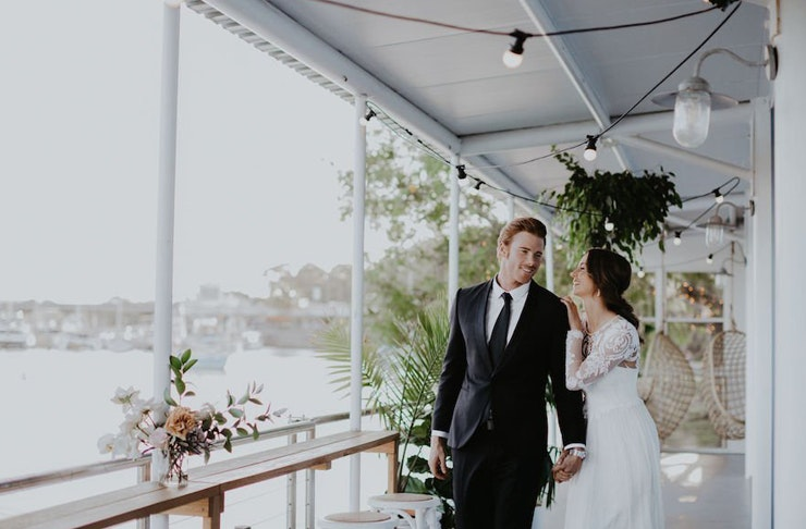 A bride and groom embrace on a waterfront balcony, under festoon lights.