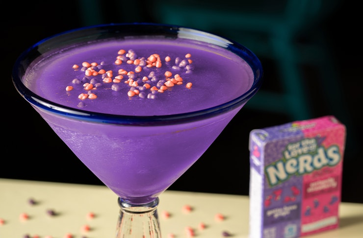 A glass filled with a frozen margarita and topped with Nerds lollies