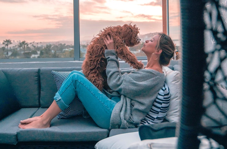 A woman sits on a rooftop couch cuddling a small fluffy dog.