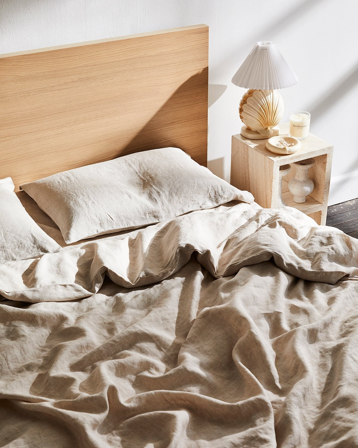 Linen sheets lay sprawled on a messy bed.