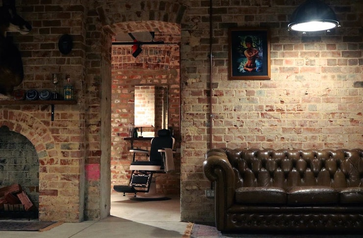 Interior of Ugly Mens Barber In Perth, exposed bricks, leather couches and a barber chair are inside.