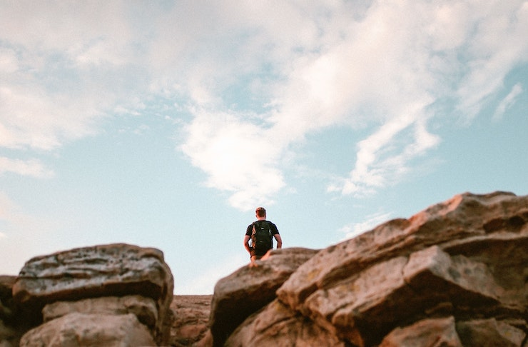 A man stands on top of a rock formation under a blue sky in the distance.