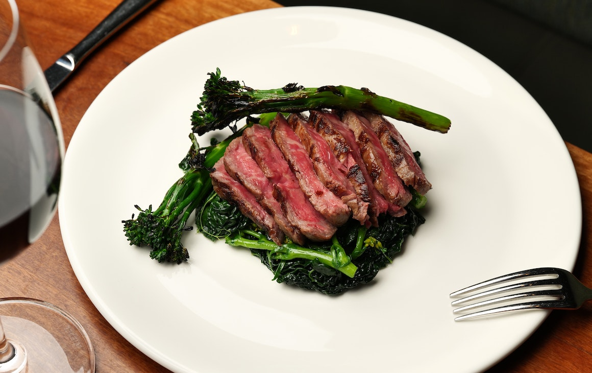 Steak on a bed of greens on a white plate