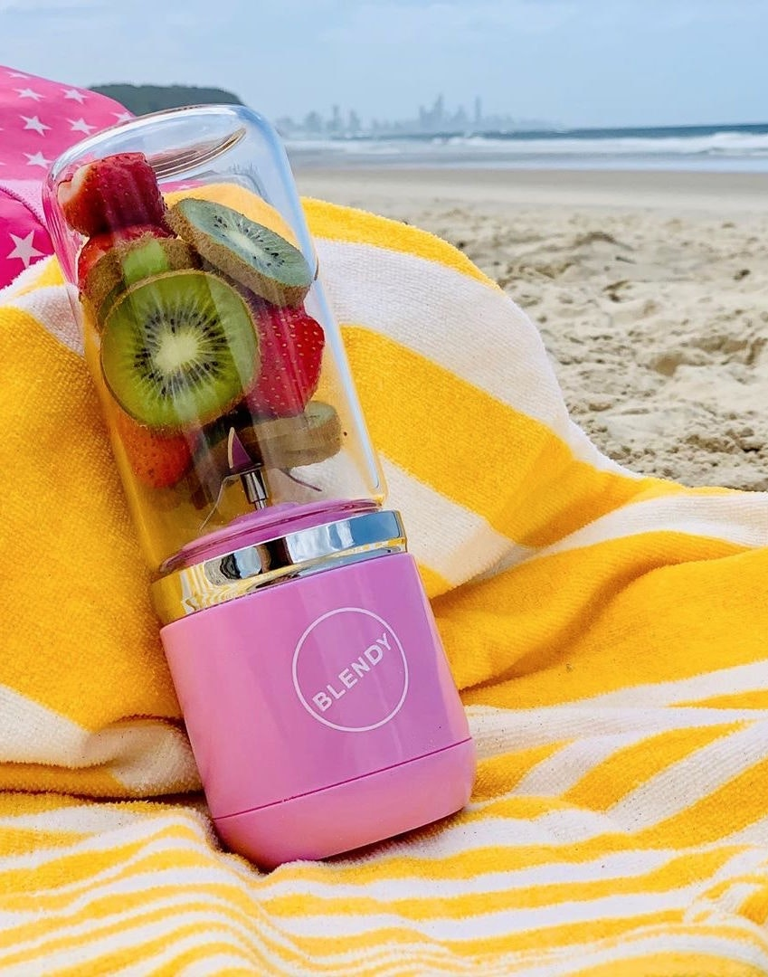 A portable blender sits on a yellow towel on the beach.