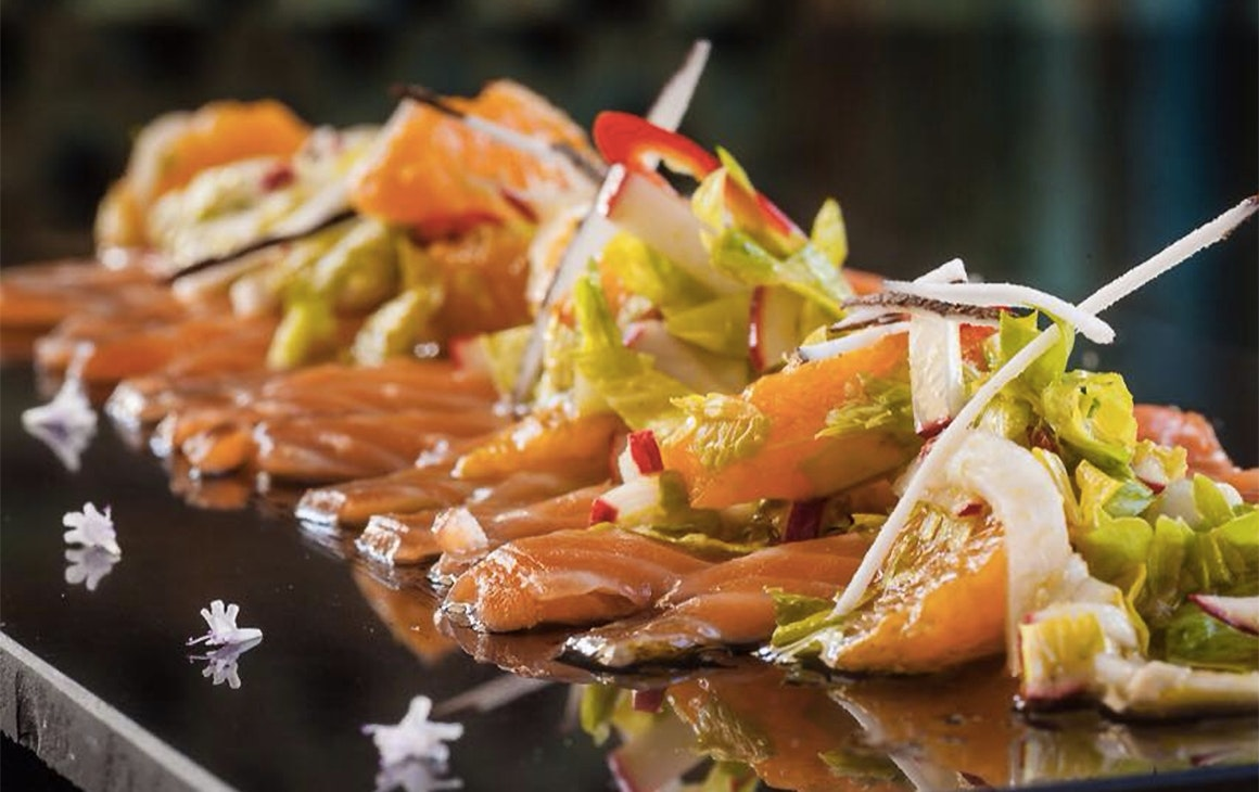 Dressed smoked salmon sits on a board with tiny flower adornments.