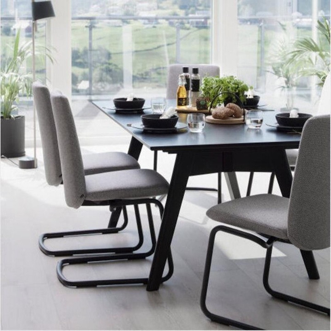 Plush chairs surround a black wooden table with thin legs.