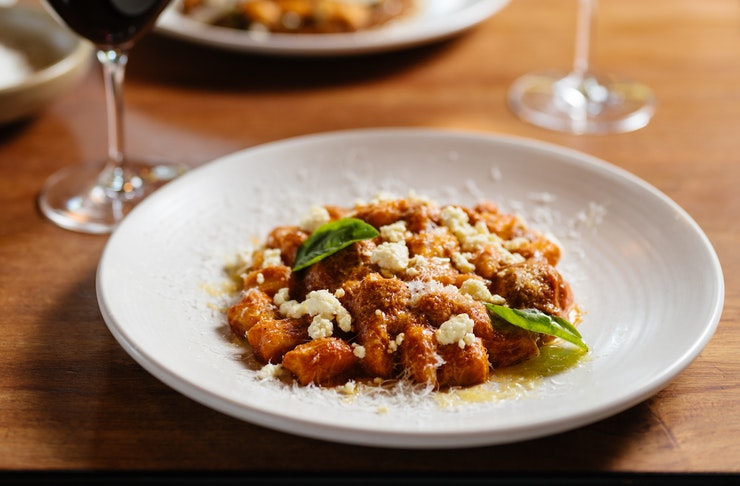 A bowl of gnocchi sits on a wooden table.