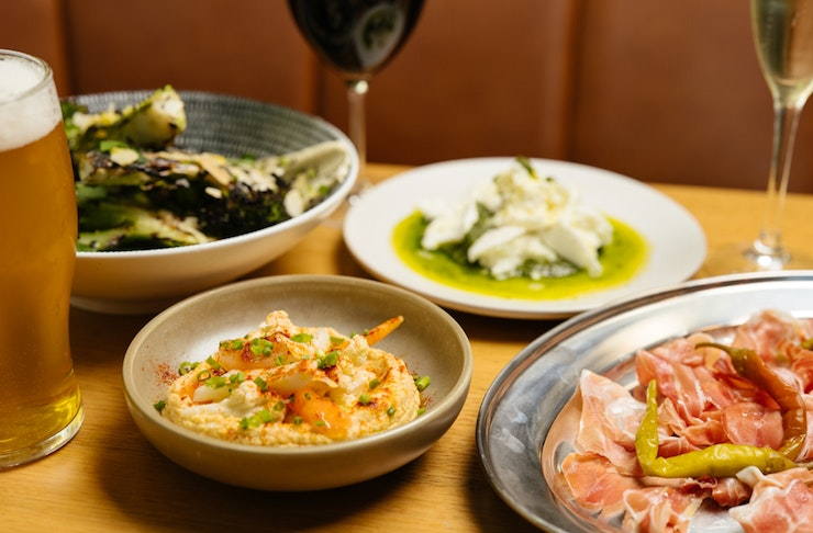 Four dishes of hummus, meat, burrata and more sit on a table with a glass of wine and beer.