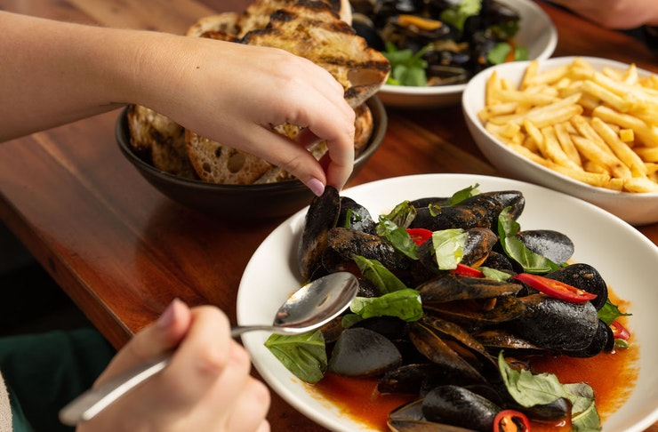 A table full with bottomless mussels. chips, bread and drinks