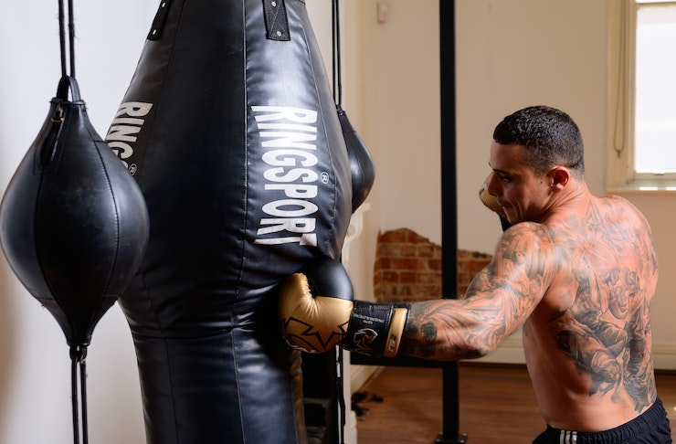 A man boxing with a punching bag.