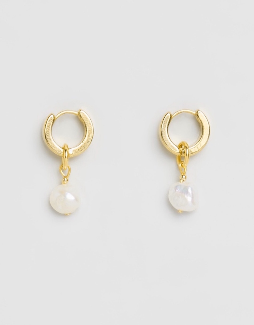 Two gold Brie Leon sleeper earrings with a pearl drop are laid down side by side.