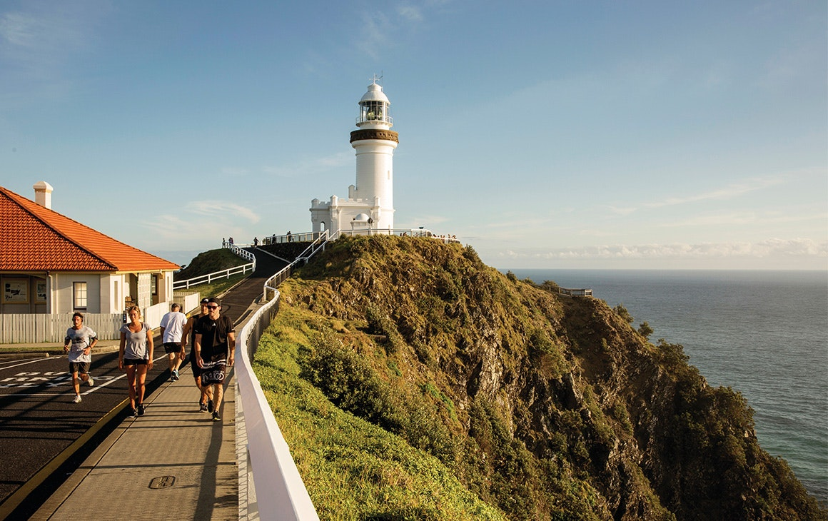 Byron Bay lighthouse, with people walking along the path towards it.