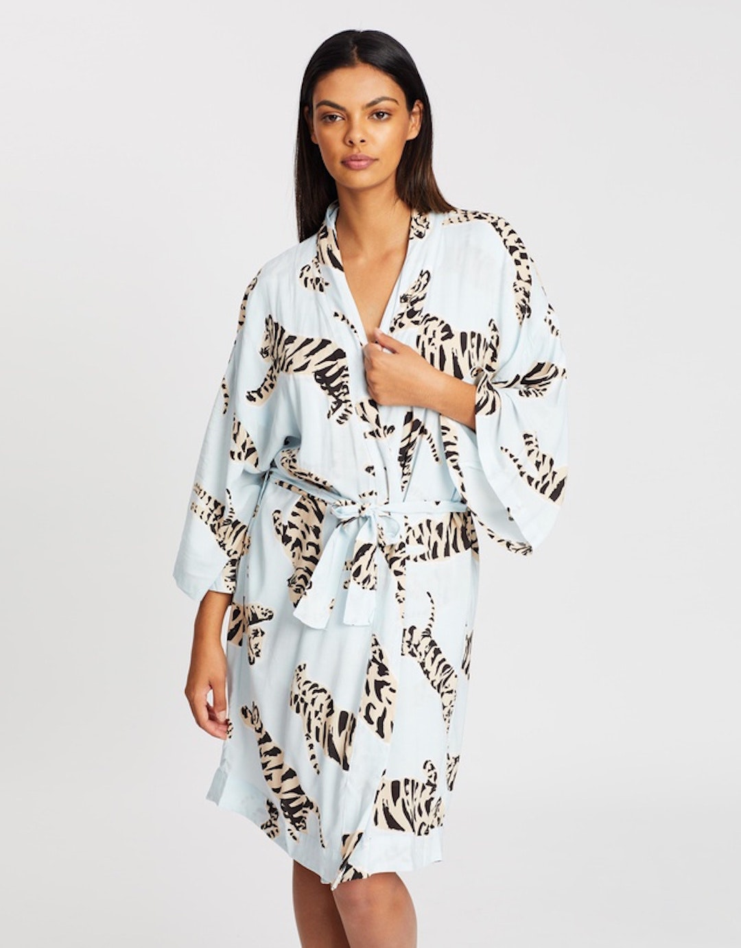 A woman poses wearing a blue dressing gown with a tiger print.