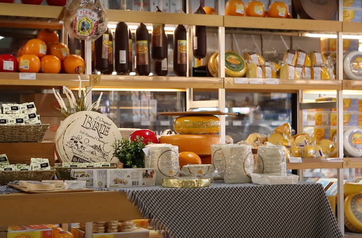 A room full of different kinds of cheese stacked on wooden shelves