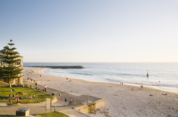 View looking out over Cottesloe Beach with people sitting on the grass and sand looking out over the beach