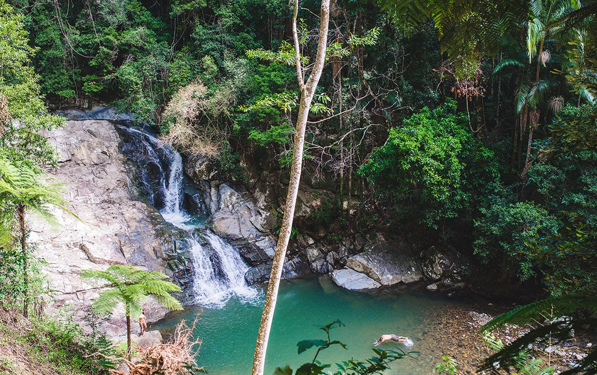 Waterfall tumbling down a rockside into an aqua pool