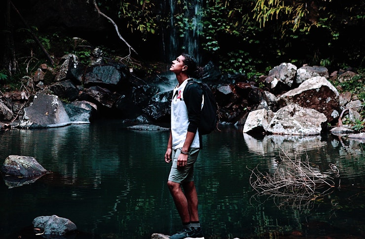 A man stands on a rock in front of a waterfall looking up towards the sky.