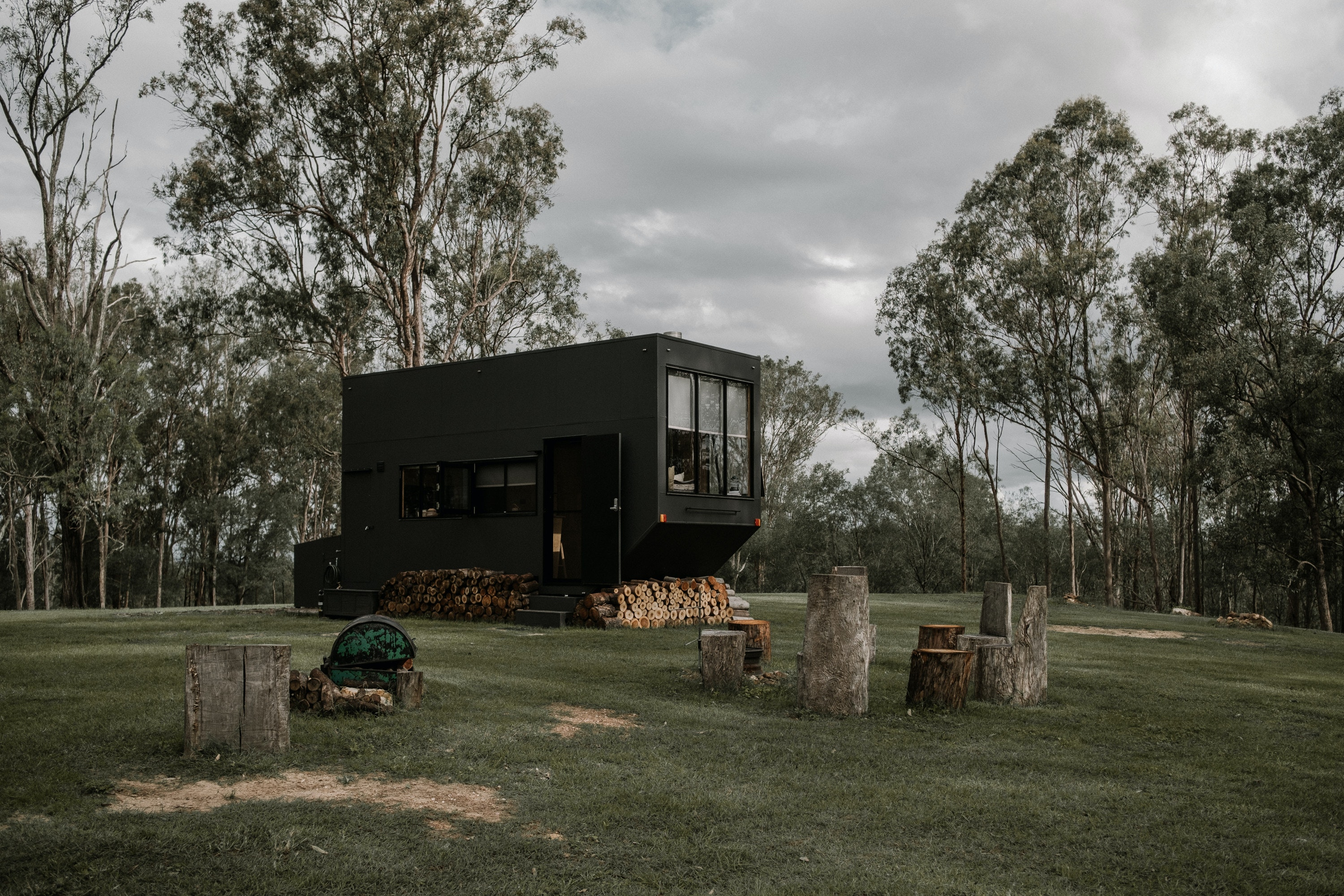 A quaint tiny home underneath gumtrees and surrounded by lush, green grass.