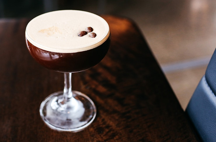 An espresso martini stands on a table looking totally delicious