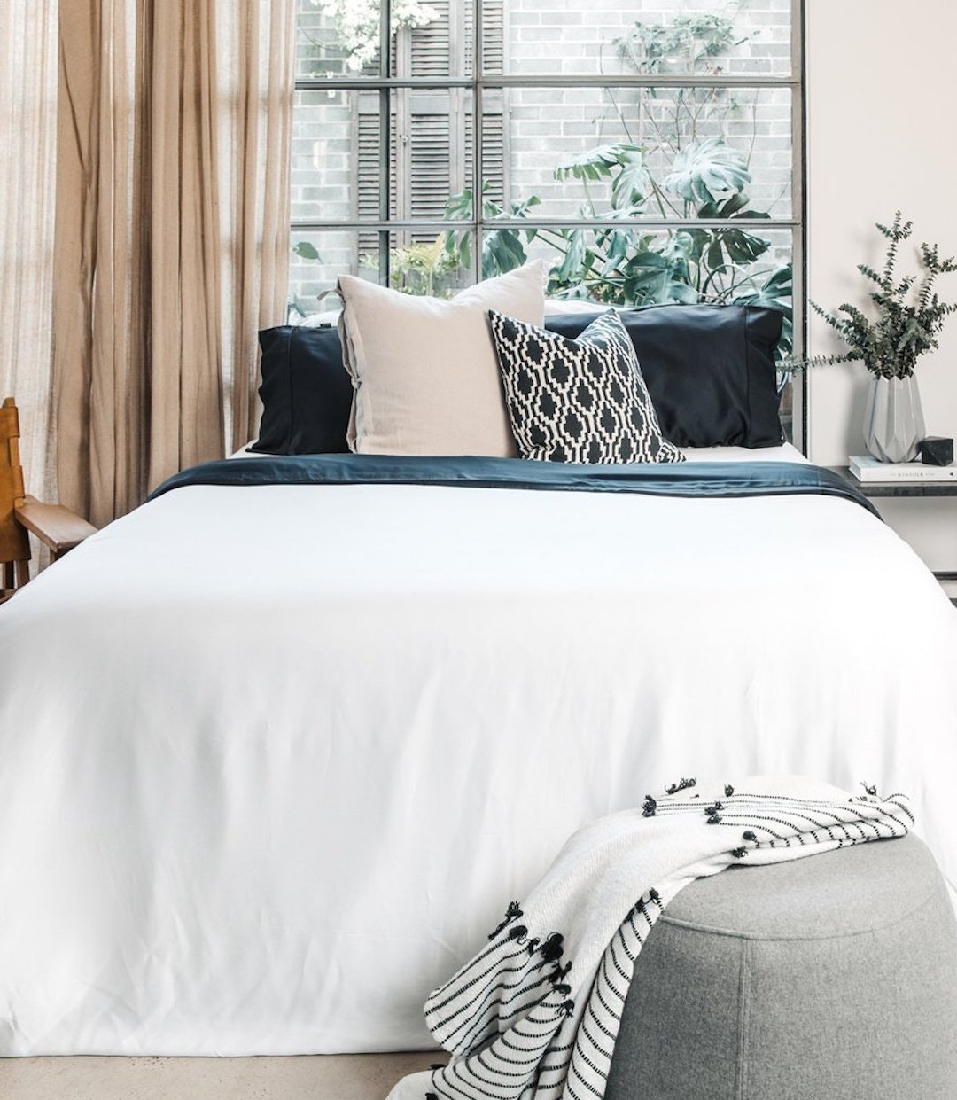 A plush and inviting blue and white bed.