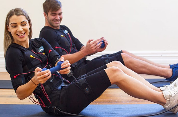 a woman smiles whilst she is holding a weight and connected to an EMS machine