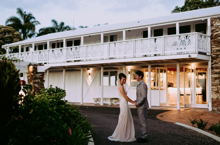A bride and groom embrace outside of a white plantation style house at Fins in Duranbah.