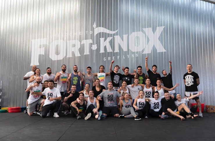 a group of happy exercise crew stand in front of the Fort Knox logo