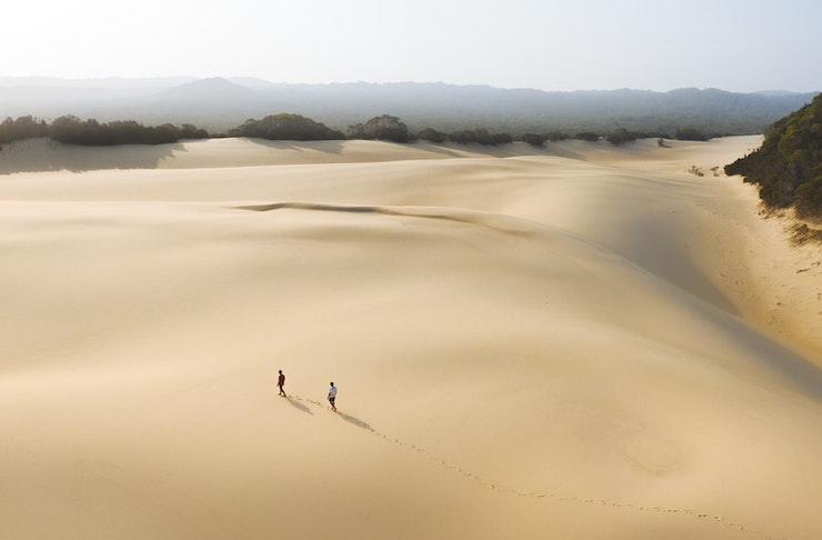 Two people trek across a vast and untouched sand blow on Fraser.