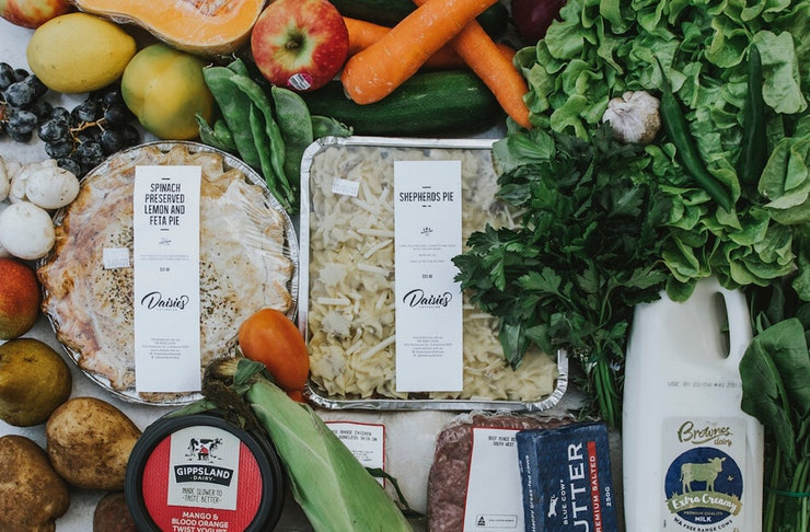 A flat lay of fruit, vegetables, milk, yoghurt and two ready made meals and more fresh produce that can be delivered in Perth