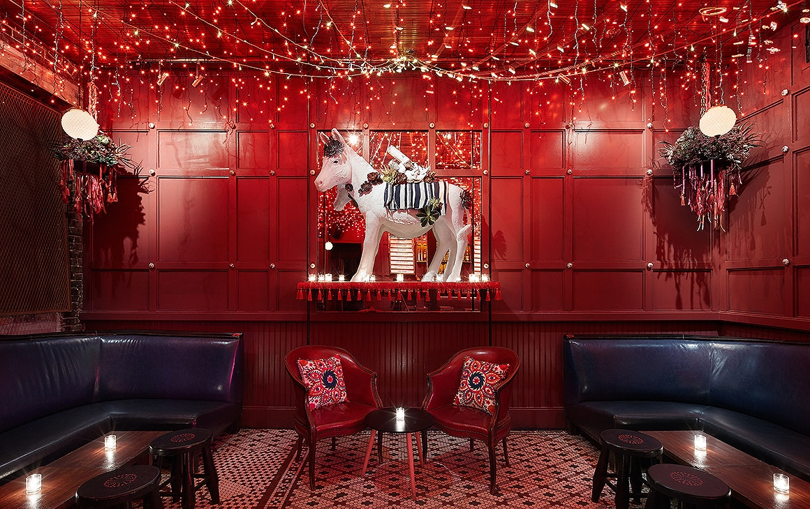 The interior at Ghost Donkey at Commercial Bay showing a gloriously red room with banquettes, red chairs and a huge donkey in the background.