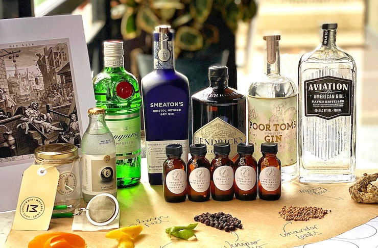 5 bottles of gin on a table with five small bottles containing botanicals in front.