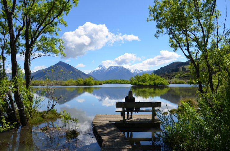 Someone sits on a peaceful bench looking out over a beautiful vista in Glenorchy.