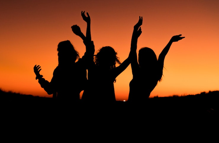 The silhouettes of three women against a sunset