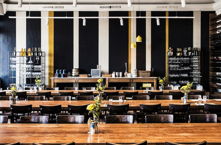 Long wooden tables and a wine wall at Il Lido