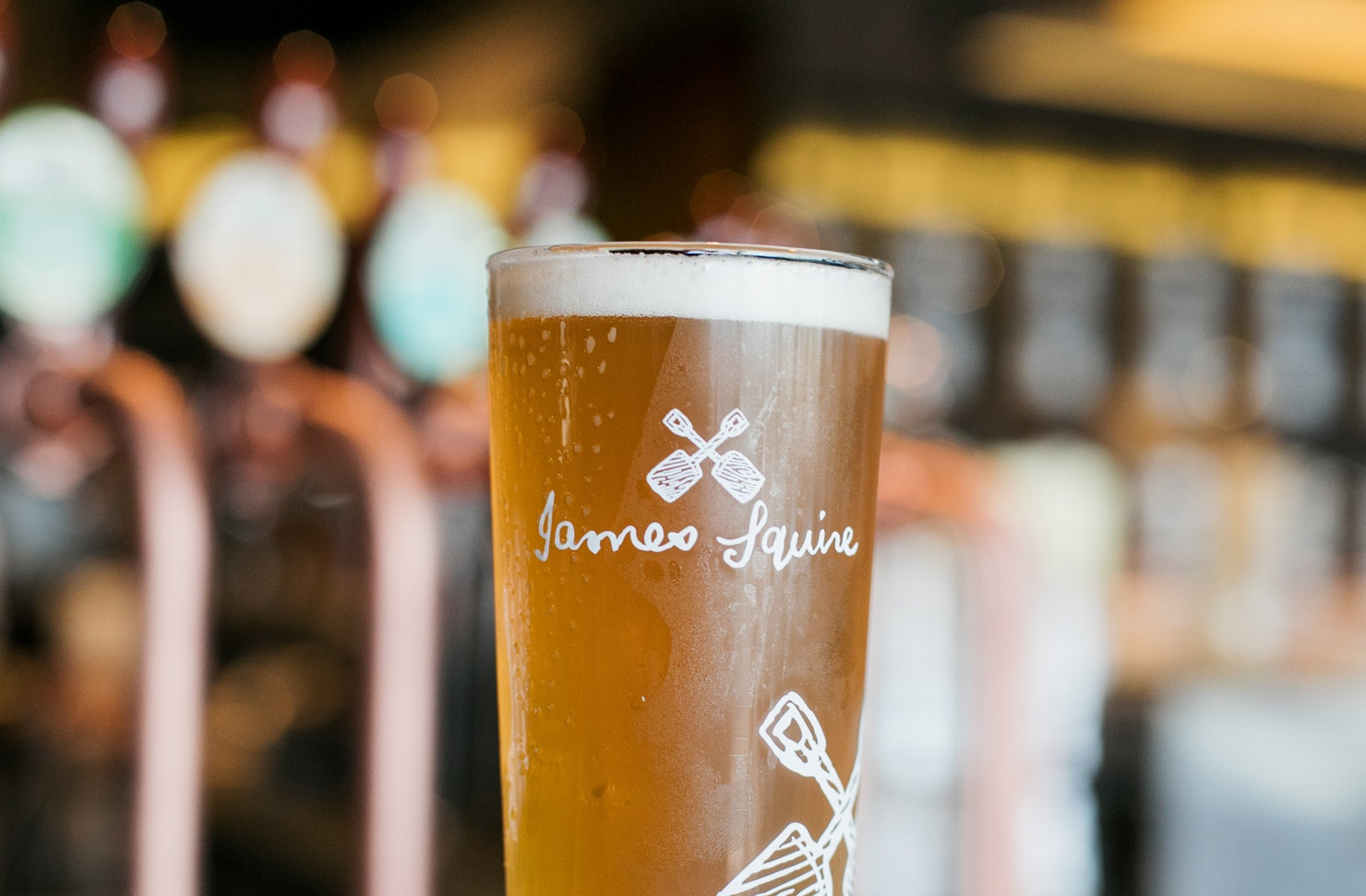 A pint with a James Squire logo is filled with a freshly-poured beer.