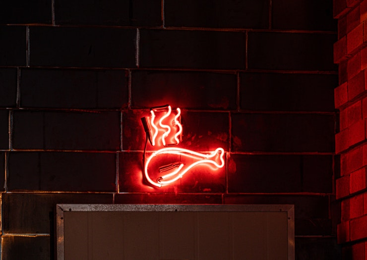 A neon drumstick sign sits above a refrigerator door.