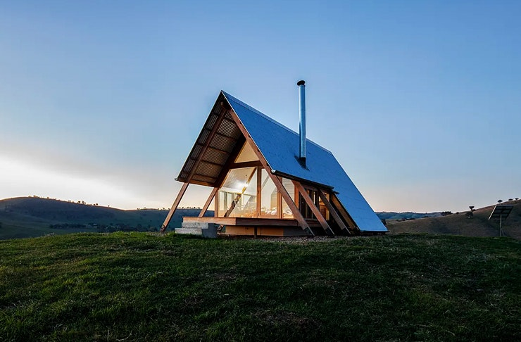 An a-frame tiny house on a hill with the sun setting in the distance.
