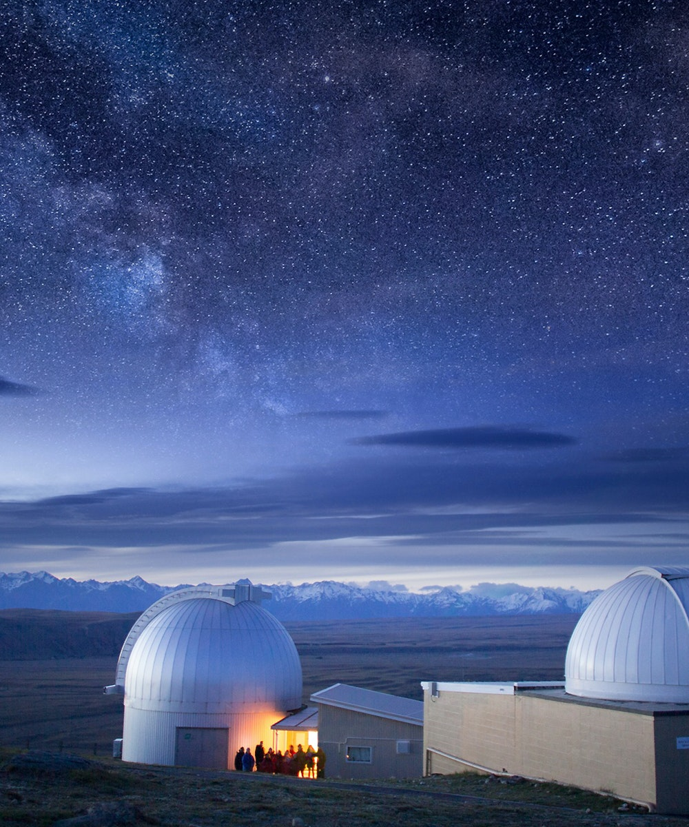 The observatory at Tekapo's Mt John Observatory showing thousands of stars illuminated in the night sky.