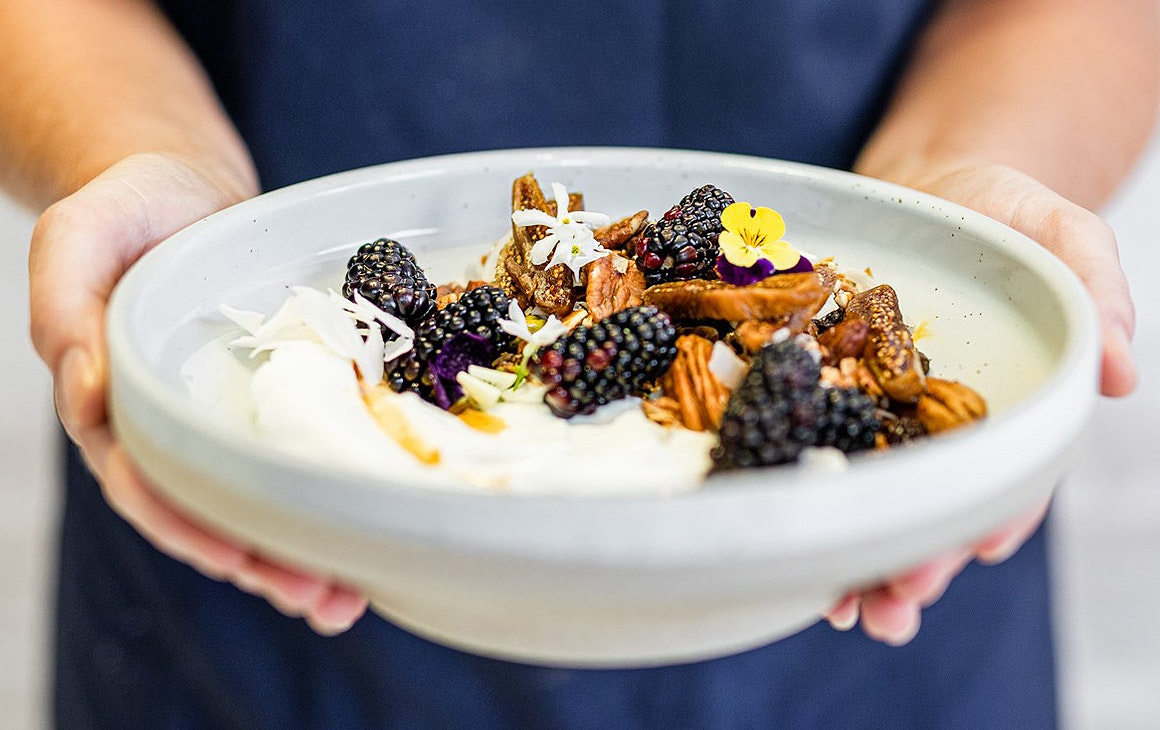 A person holds out a lovely looking dish of berries aloft at Lieutenant Coffee Bar & Eatery in Commercial Bay