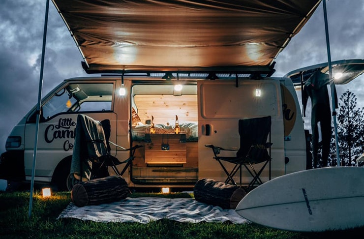 A shot at dusk of a lit up camper van with camping chairs positioned under an open awning.