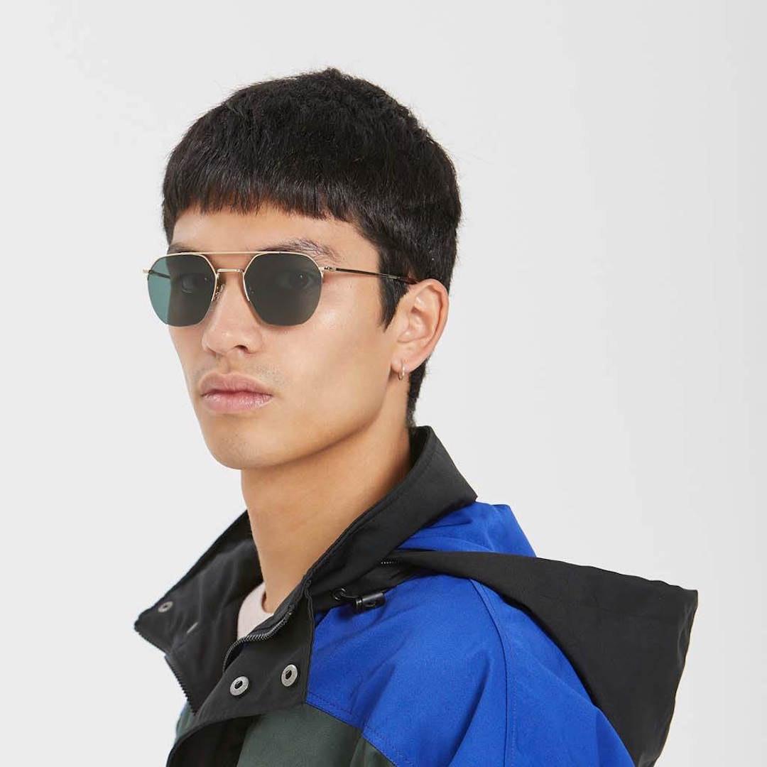 A man wears a blue puffer jacket and aviator sunglasses.