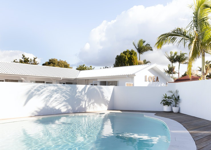 White exterior of LOEA Hotel on the Sunshine Coast, with their magnesium pool in the foreground.