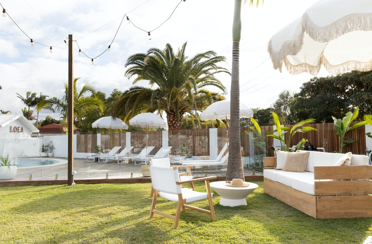 A garden decked out with festoon lights, palms and white furniture and beach umbrellas.