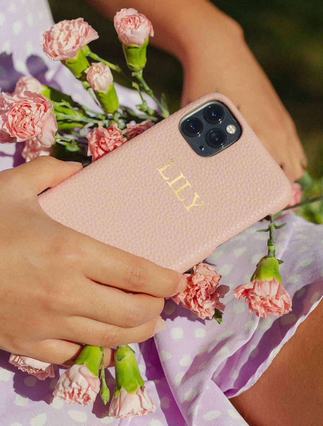 A woman holds a pink phone case and pink flowers.