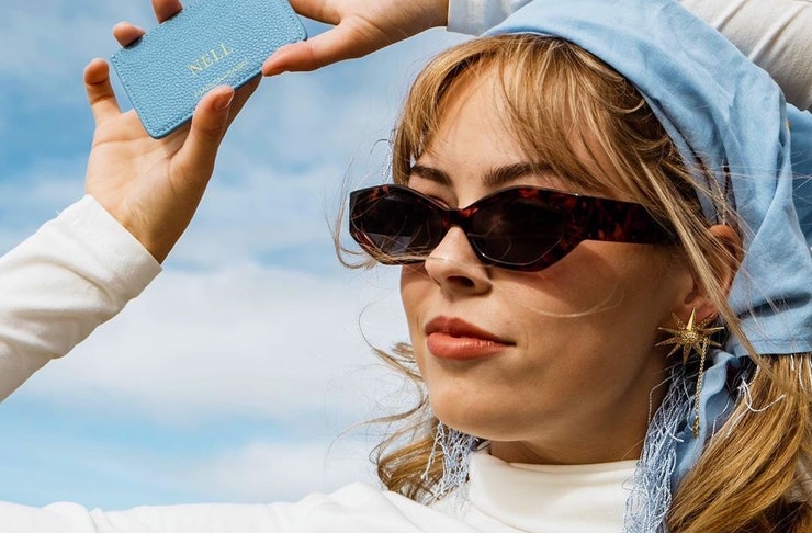 A woman wears a blue headscarf and black sunglasses and holds a blue cardholder accessory to the sky.